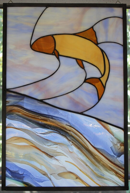 Brown fish jumping from river, stained glass panel